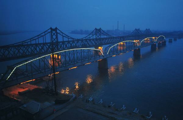 Dusk falls over the Yalu River, which separates the North Korean town of Siniuju (opposite) from the Chinese city of Dandong, as lights are turned on along the Yalu River bridge, also known as the no-name bridge. The full-length bridge built right beside the no-name bridge remains busy during the day time as trucks, trains and other vehicles transport goods back and forth (Frederic J. Brown/AFP/Getty Images