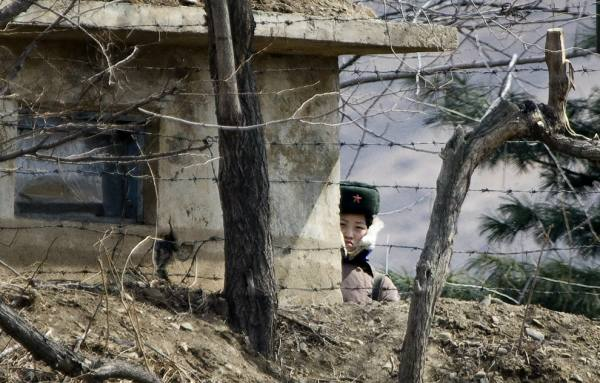 A North Korean soldier stands watch from behind her guard post on the waterfront of the Yalu River (AP Photo/Andy Wong)